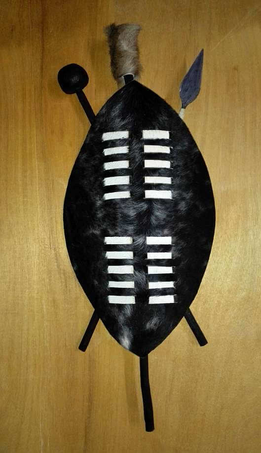 A black Zulu shield with white stripes in a grid pattern